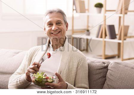 Healthy Eating. Happy Senior Man Eating Fresh Vegetable Salad, Sitting On Sofa At Home