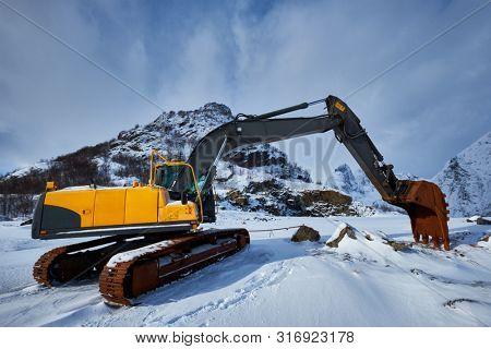 Old excavator with excavator bucket in winter. Road construction in snow. Lofoten islands, Norway