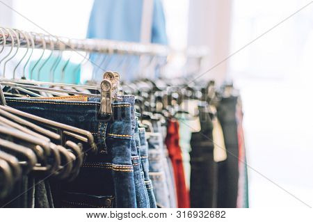Colorful Trend Women Dresses, Pants  On Hangers In Retail Shop, Store. Fashion And Shopping Concept.