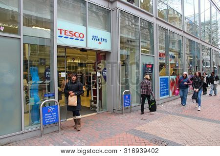 Birmingham, Uk - April 19, 2013: People Walk By Tesco Metro Branded Grocery Store In Birmingham, Uk.