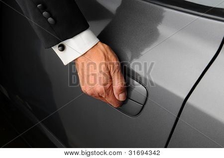 Closeup of a mans hand on the latch of a car door. Person is wearing a tuxedo.