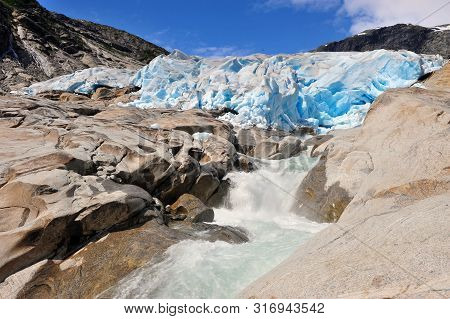 Nigardsbreen And Rocky Stream In Mountains
