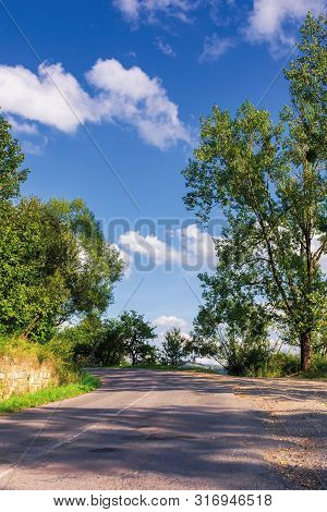 Road Uphill Through Forest. Beautiful Autumn Scenery With Trees In Green Foliage. Amazing September