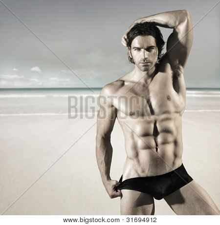 Sexy portrait of a hot buff male fitness model pulling at his bikini briefs on the beach