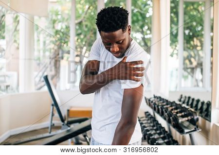 Side View Of Muscular African American Man Standing And Suffering From Shoulder Pain During Workout