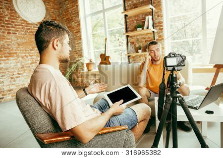 Two Young Caucasian Male Bloggers In Casual Clothes With Professional Equipment Or Camera Recording