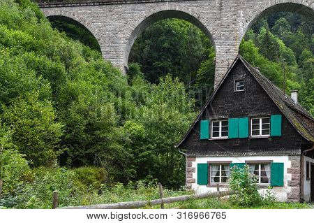 Quaint German House With Green Shutters By Old Train Trestle In Black Forest Mountains