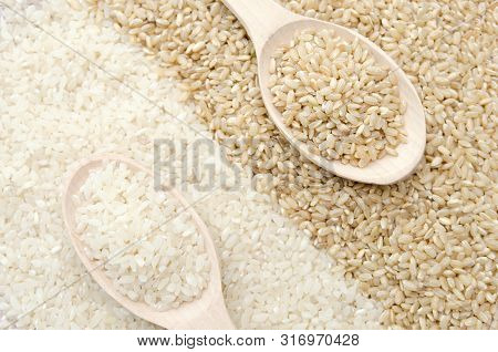 Unpolished brown rice and white polished rice in wooden spoon. Long grain rice and round grain rice background. Rice pattern. Brown rice. Rice background. Raw rice