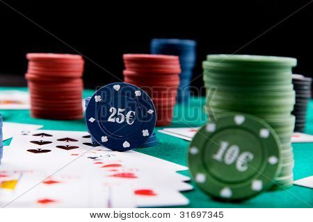 Poker chips and cards on a green fel
