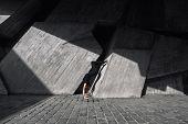 women in black doing acrobatic stunt against grey concrete modernist background poster