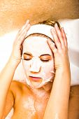 Woman putting face mask on sheet while bathing in bubble. Complexion care. poster