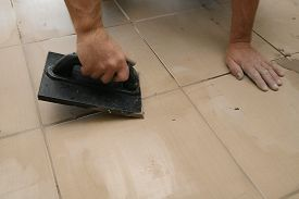 Worker Putting Fugue On Tiles On The Floor In Corridor. Grouting Ceramic Tiles, Close Up
