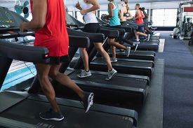 Low section of diverse fit people exercising on treadmill in fitness center. Bright modern gym with fit healthy people working out and training