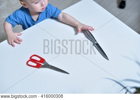 Danger In The Home, Sharp Objects Are Dangerous For Young Children. Little Boy Knife Up Scissors Fro