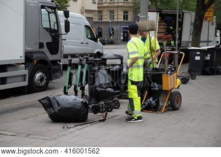 Stockholm, Sweden - June 7, 2019: Worker Cleaning Trash On Street. Professional Street Cleaner Takes