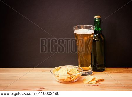 Glass Of  Beer, Bottle Of Beer And Potato Chips On Wooden Table On Dark Background. Selective Focus.