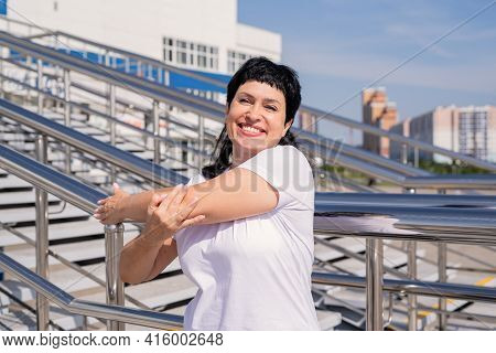 Smiling Senior Woman Doing Stretching Outdoors On Urban Background