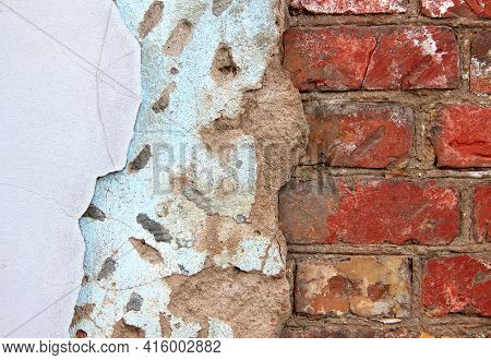 An Old Damaged Brick Wall Partially Covered With Two Layers Of Plasterwork