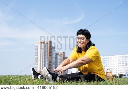 Senior Woman Stretching Her Legs On Grass In The Park On Urban Background