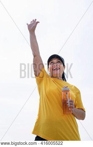 Excited Senior Woman Saying Hello Drinking Water After Workout Outdoors On The Sports Ground