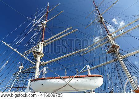 Masting And Rigging Of An Old Classical Sailing Boat With A Lifeboat Against A Blue Sky