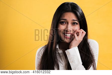 Young Excited Woman Chews On Her Fingernails - Studio Photography