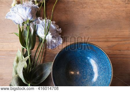 Porcelain Set On A Wooden Table. Wooden Spoon In A Blue Plate. Blue And White Plates With Flowers