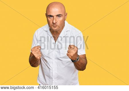 Mature middle east man with mustache wearing casual white shirt ready to fight with fist defense gesture, angry and upset face, afraid of problem