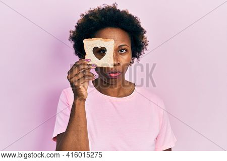 Young african american woman holding bread loaf with heart shape skeptic and nervous, frowning upset because of problem. negative person.