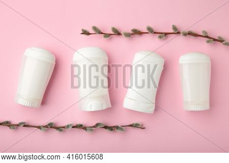 White Deodorants With Willow Twigs On Pink Background. Top View.