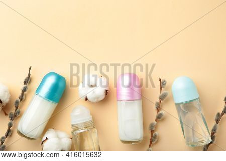 White Deodorants With Willow Twigs On Beige Background. Top View.