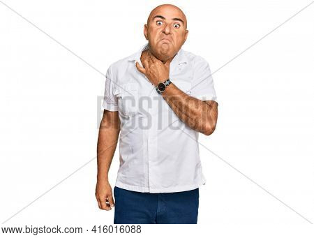 Mature middle east man with mustache wearing casual white shirt touching painful neck, sore throat for flu, clod and infection