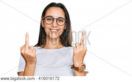 Young hispanic woman wearing casual white t shirt showing middle finger doing fuck you bad expression, provocation and rude attitude. screaming excited