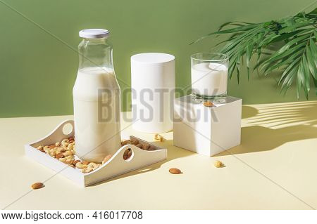Glass With Vegan Milk From Various Nuts With A Bottle On White Wooden Tray On Sunlit Background With