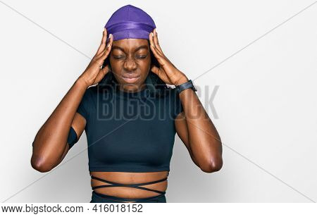 Young african american woman wearing sportswear suffering from headache desperate and stressed because pain and migraine. hands on head.