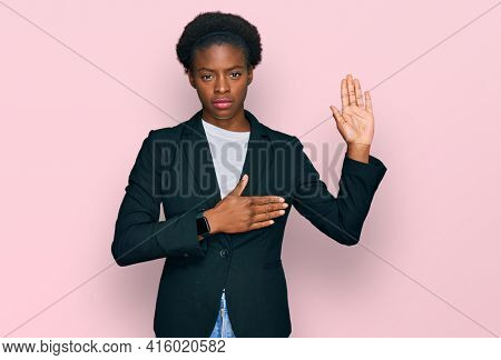 Young african american girl wearing business clothes swearing with hand on chest and open palm, making a loyalty promise oath