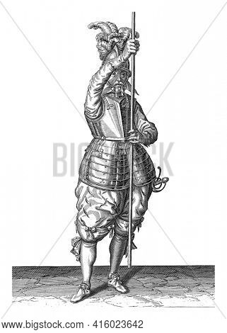 A full-length soldier holding a skewer (lance) with both hands upright in front of him slightly above the ground, this is the second act of placing the skewer on the ground, vintage engraving.