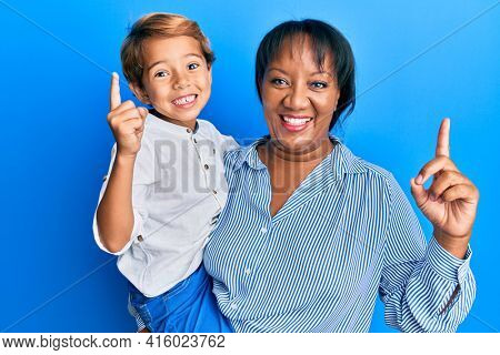Hispanic family of mother and son hugging together with love smiling with an idea or question pointing finger with happy face, number one