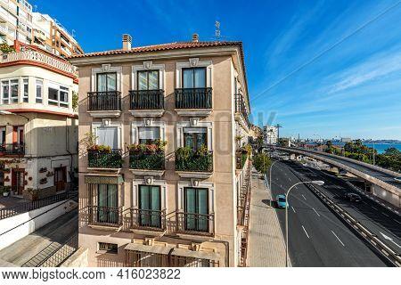 Beautiful houses along freeway under blue sky in Alicante, Spain.