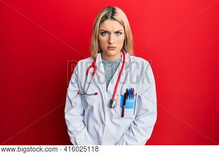 Young caucasian woman wearing doctor uniform and stethoscope skeptic and nervous, frowning upset because of problem. negative person.