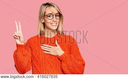 Beautiful blonde woman wearing casual clothes and glasses smiling swearing with hand on chest and fingers up, making a loyalty promise oath