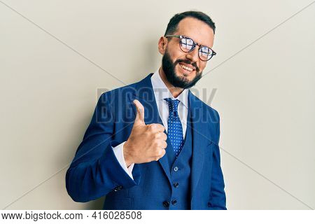Young man with beard wearing business suit and tie doing happy thumbs up gesture with hand. approving expression looking at the camera showing success.