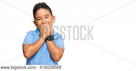 Little boy hispanic kid wearing casual clothes laughing and embarrassed giggle covering mouth with hands, gossip and scandal concept