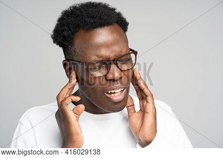 Sick African American Millennial Man Suffering From Tinnitus, Throbbing Earache, Tired Of Noise. Irr