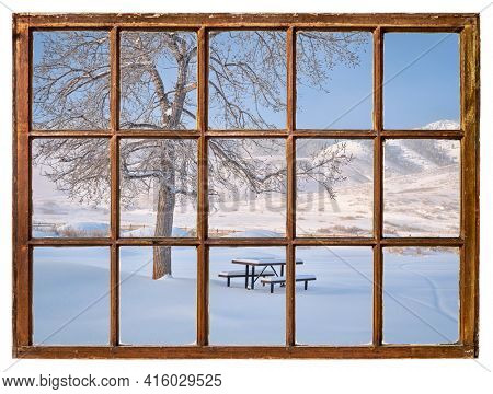 picnic table covered by fresh snow at foothills of Rocky Morning as seen from a vintage sash window