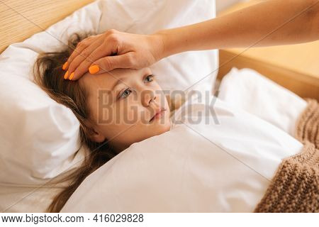 Close-up View Of Young Mother Measures Temperature Touches Forehead Of Sick Daughter Lying In Bed At