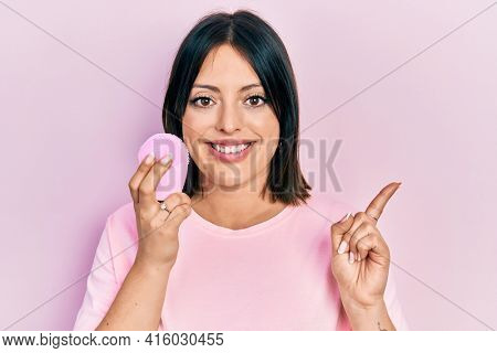 Young hispanic woman using facial exfoliating cleaner smiling happy pointing with hand and finger to the side