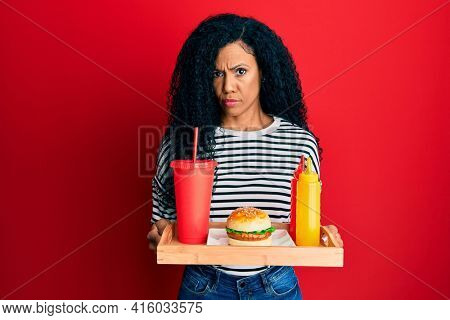 Middle age african american woman eating a tasty classic burger skeptic and nervous, frowning upset because of problem. negative person.