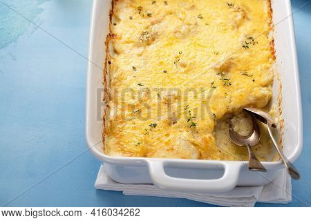 Cheesy Baked Potatoes In A Baking Dish With Thyme