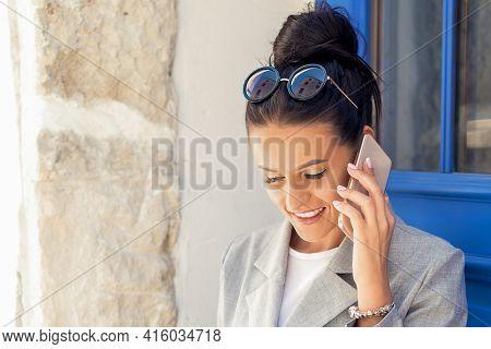 Portrait Of Happy Attractive Young Businesswoman Talking On Smart Phone Near Door Outdoors.